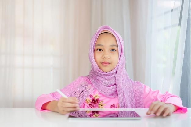 Muslimisches mädchen trägt rosa hijab und benutzt ihr tablet zu hause