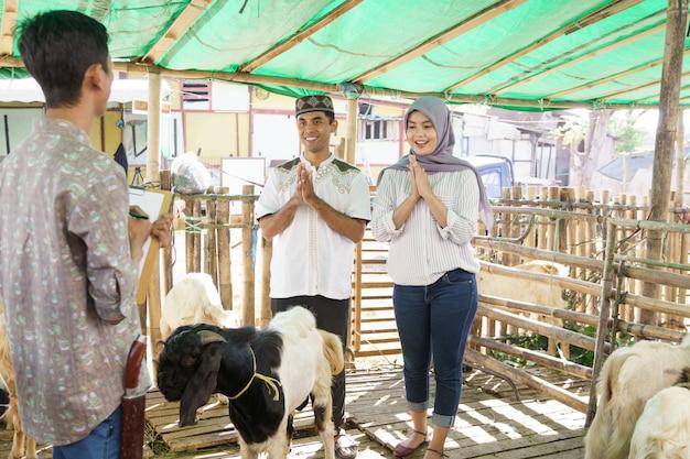 Muslimisches paar auf der tierhandelsfarm, das eine ziege für eid adha opferzeremonie kauft