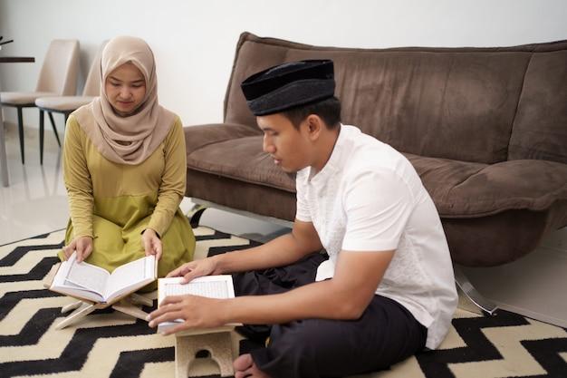 Muslimisches paar, das den heiligen koran liest