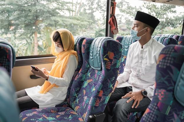Muslimisches paar, das masken trägt und während des eid mubarak urlaubs mit dem bus fährt, um familie zu hause zu treffen