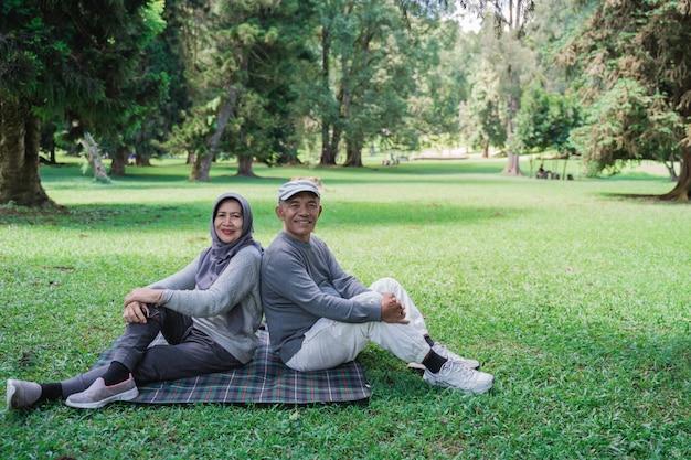 Muslimisches paar im park lächelnd und kamera betrachtend