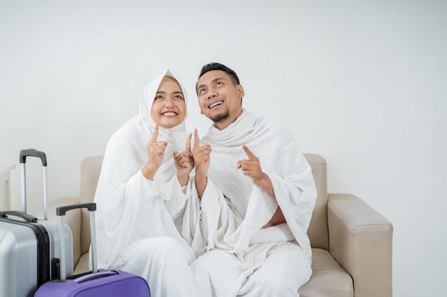 Muslimisches paar sitzt in weißer traditioneller kleidung vor umrah
