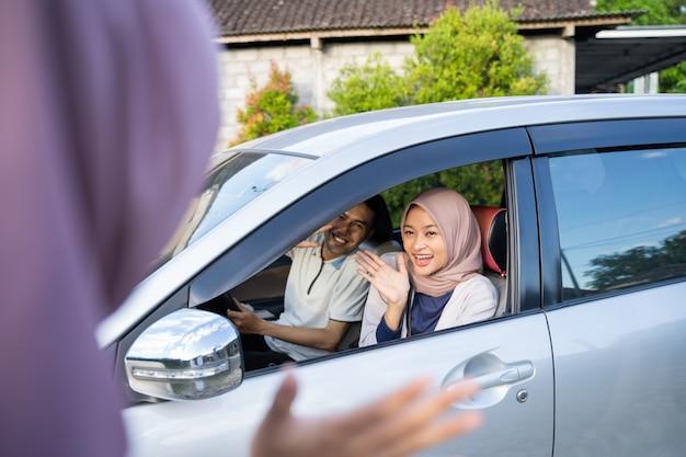 Muslimisches paar winkt einer frau mit hijab aus dem auto zu