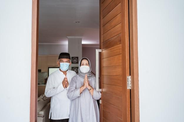 Muslimisches reifes paar, das gesichtsmaske trägt, die an der haustür ihres hauses mit grußgeste steht