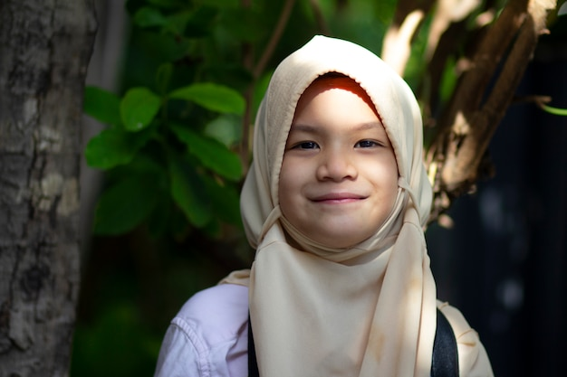 Muslimisches schulkind. hübsches kleines mädchen im hijab mit digitalkamera.