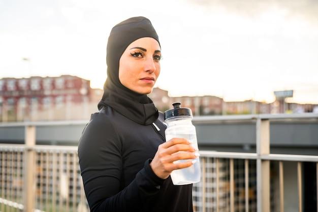 Muslimisches sportliches mädchen mit fitem körpertraining außerhalb