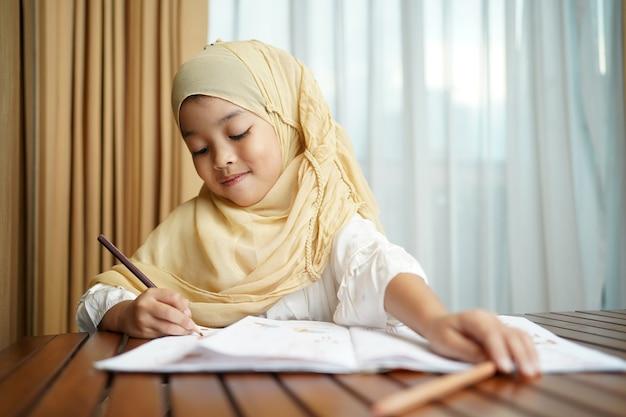 Muslimisches studentenkindmädchen, das auf dem papierbuch schreibt.