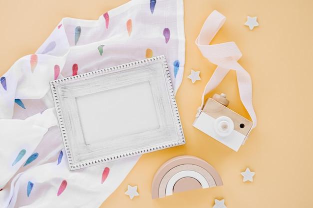 Musselin wickeldecke mit fotorahmen und babyspielzeug auf gelbem hintergrund. set mit geschlechtsneutralem neugeborenenzubehör. flache lage, ansicht von oben