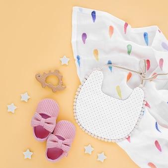 Musselin wickeldecke mit lätzchen, schuhen und babyspielzeug auf gelbem hintergrund. set von sachen und zubehör für neugeborene. flache lage, ansicht von oben