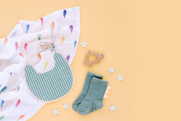 Musselin wickeldecke mit lätzchen, socken und babyspielzeug auf gelbem hintergrund. set von sachen und zubehör für neugeborene. flache lage, ansicht von oben