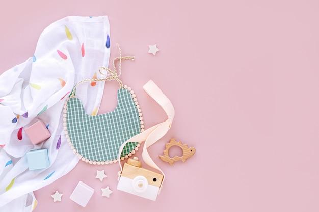 Musselin wickeldecke mit lätzchen und babyspielzeug auf rosa hintergrund. set von sachen und zubehör für neugeborene. flache lage, ansicht von oben