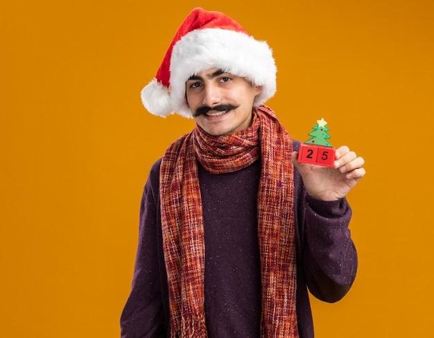 Mustachioed mann, der weihnachtsweihnachtsmütze mit warmem schal um seinen hals trägt, der spielzeugwürfel mit datum fünfundzwanzig betrachtet kamera mit lächeln auf gesicht, das über orange hintergrund steht Kostenlose Fotos