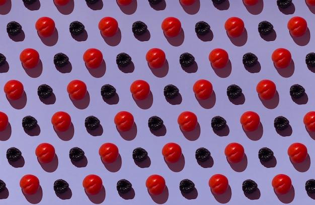 Muster auf einem lila hintergrund mit reifen roten pflaumen und hölzernen untersetzern mit grünen blättern mit holzhintergrund