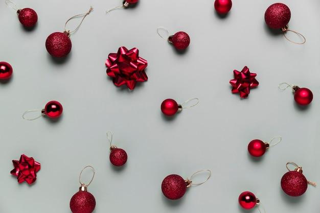 Muster auf grauem hintergrund mit kleinen roten weihnachtskugeln oder kugelspielzeug, bandschleifen für tannenbaum. konzept für festliche grußkarte oder einladung zur weihnachtsfeier. foto in hoher qualität