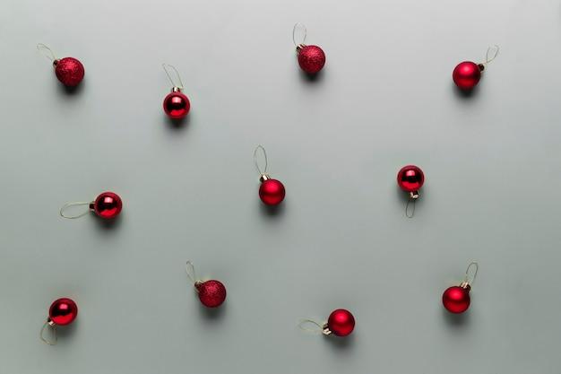 Muster auf grauem hintergrund mit kleinen roten weihnachtskugeln oder kugelspielzeug für tannenbaum. konzept für festliche minimalistische grußkarte oder einladung zur weihnachtsfeier. foto in hoher qualität