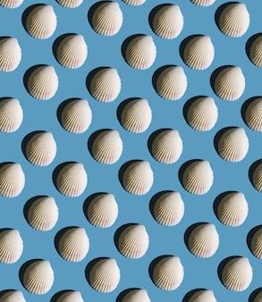 Muster aus muscheln mit hartem schatten auf blauem hintergrund, ansicht von oben.