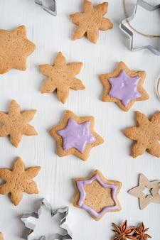 Muster aus süßen herzhaften lebkuchenplätzchen mit violettem zuckerguss auf weißem holztisch