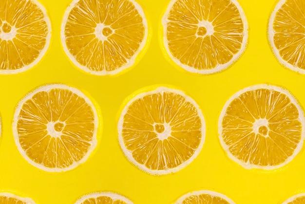 Muster der frisch geschnittenen zitrone auf gelbem hintergrund. zitronen früchte. saftige zitronenscheibe auf gelbem hintergrund.