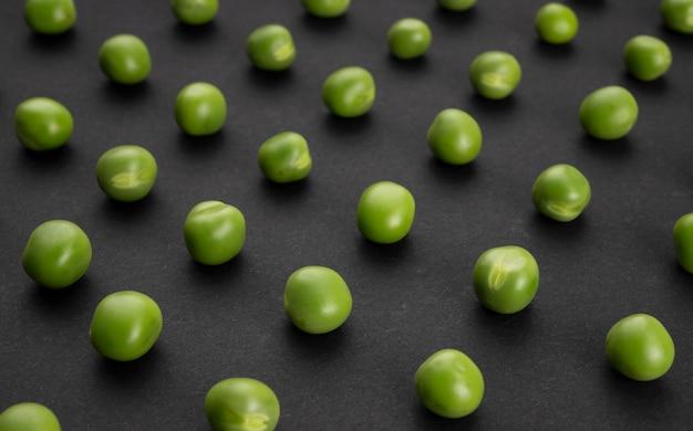 Muster der frischen grünen erbsen auf schwarzem hintergrund, draufsicht