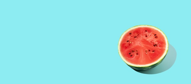 Muster der geschnittenen frischen wassermelone auf blauem hintergrund. sommerfrucht, beere. kräftige farben. trendy, minimale schatten. wassermelonen-tageskonzept - 3. august. platz kopieren.