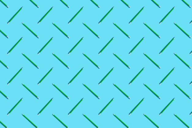 Muster der grünen stifte. das konzept von büro, business, kreativität, training. blauer hintergrund, draufsicht, flache lage.