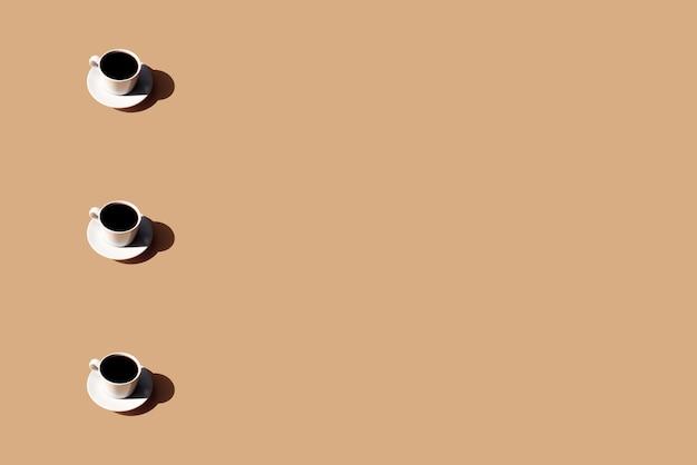 Muster der kaffeetasse und des tellerschattens der sonne auf beigem terrakottahintergrund