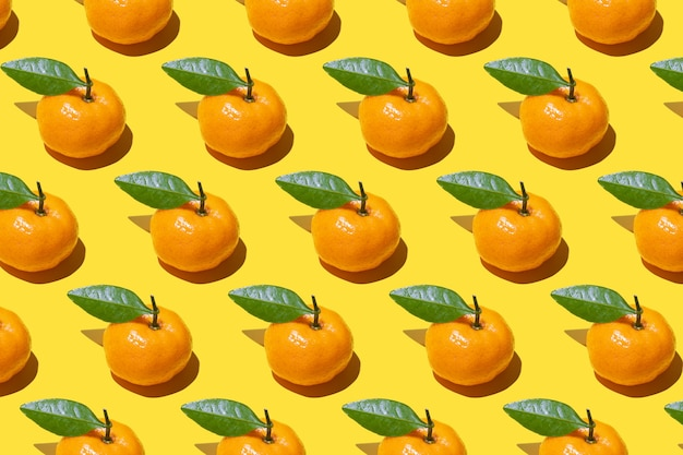Muster der reifen mandarinen mit grünen blättern auf einem gelben