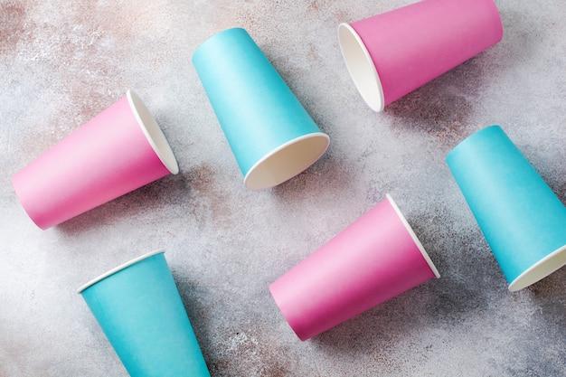 Muster der rosa und blauen pappbecher kaffee auf alter heller oberfläche. flach liegen.
