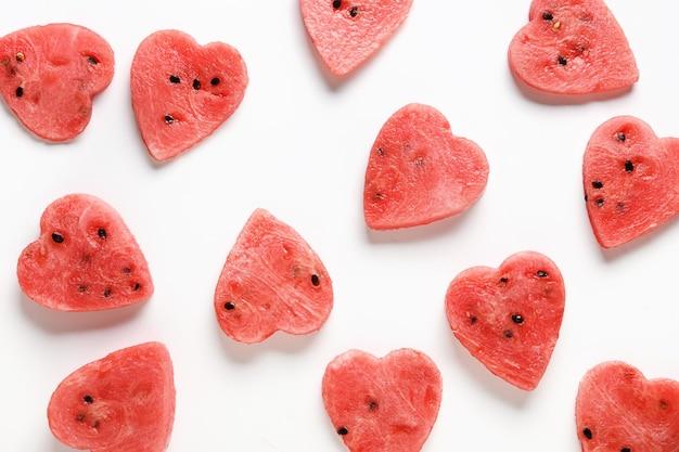 Muster der wassermelonenscheiben als herzen auf weißem hintergrund. flach liegen. lebensmittelkonzept für valentinstag.