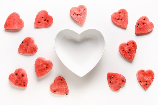 Muster der wassermelonenscheiben als herzen auf weißem hintergrund. flach liegen. valentinstag. speicherplatz kopieren.