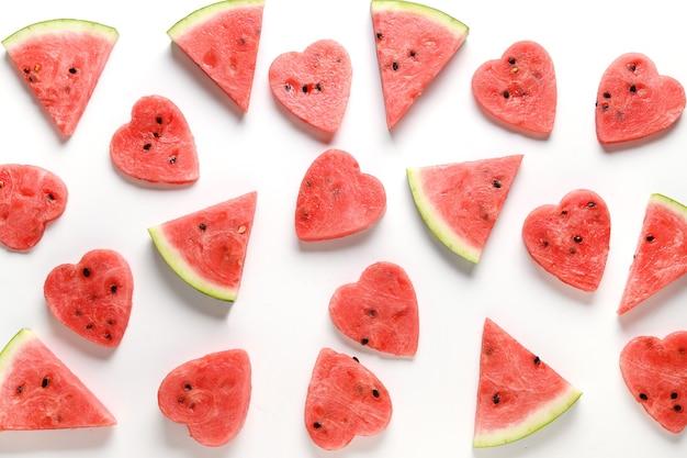 Muster der wassermelonenscheiben auf weißem hintergrund. flach liegen. lebensmittelkonzept für valentinstag.
