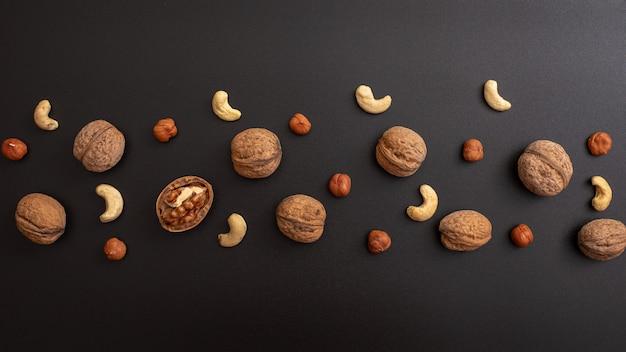 Muster geschälte walnuss, haselnuss und cashewnüsse auf schwarzem tisch.