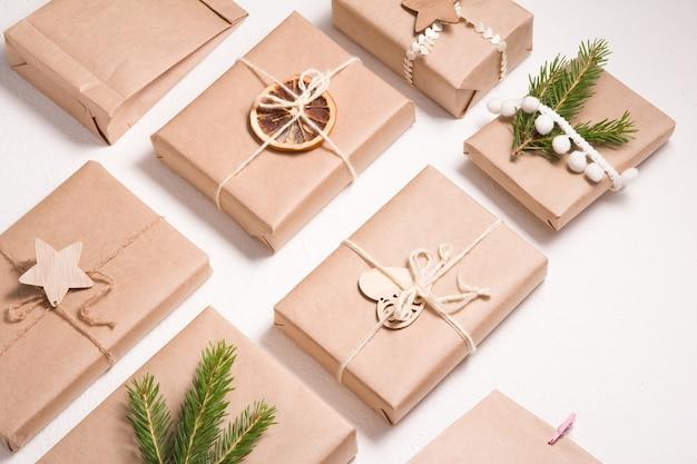 Muster mehrerer weihnachtsgeschenkboxen im umweltfreundlichen stil auf weißem hintergrund, dekor aus holzspielzeug für weihnachtsbaum, getrockneter orangen- und fichtenzweig