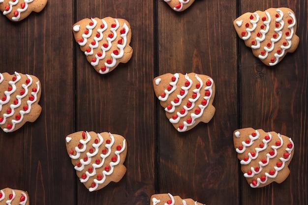 Muster mit keksen geformten weihnachtsbaum auf einem dunklen hölzernen hintergrund