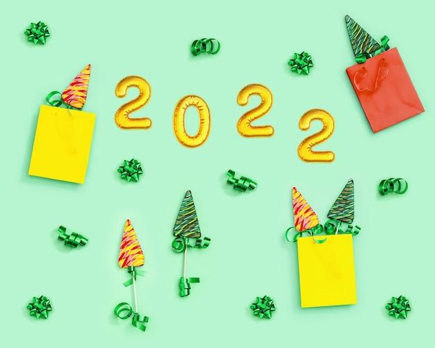 Muster mit lutscher als weihnachtsbaum und metallischen goldenen ziffern 2022 helle bonbons in papiertüte