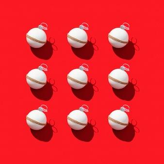 Muster mit weißen neujahrskugeln, feiertagsspielzeug auf leuchtendem rot.