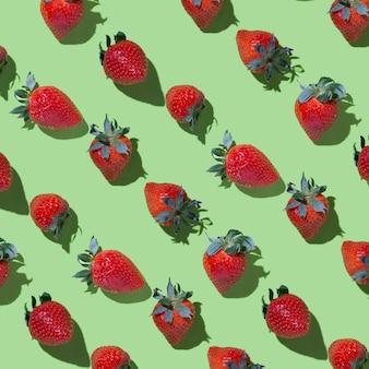 Muster, reife erdbeeren auf grünem hintergrund mit harten schatten