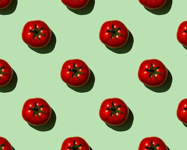 Muster rote tomaten auf grünem hintergrund