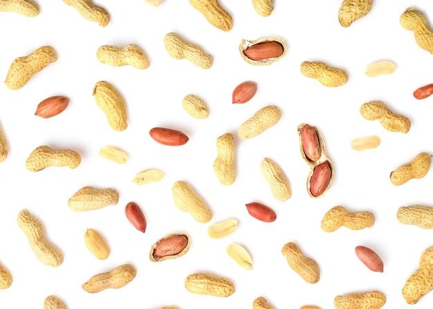 Muster von erdnüssen in nussschale, ungeschälte und geschälte erdnüsse isoliert auf weiß