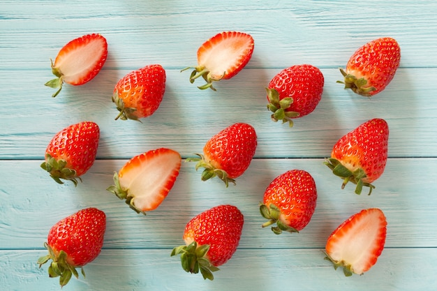Muster von ganzen und halbierten erdbeeren auf türkisfarbenem bretttisch. flach liegen. draufsicht.