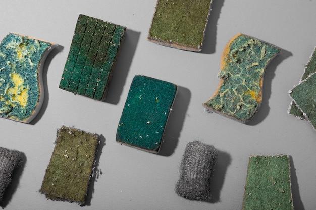 Muster von grünen schwämmen zum reinigen und spülen von geschirr auf grauem hintergrund