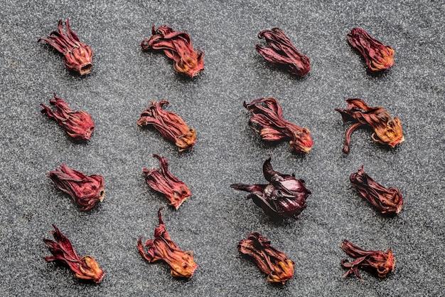 Muster von hibiscus-trockenblumen (roselle, karkade) und von einem frisch auf schwarzem steinhintergrund.