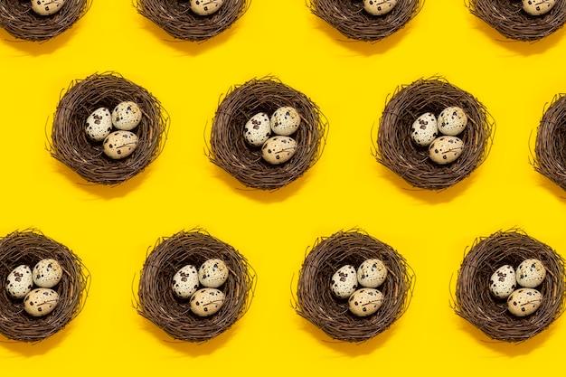 Muster von nestern mit wachteleiern auf gelbem grund. osterkonzept