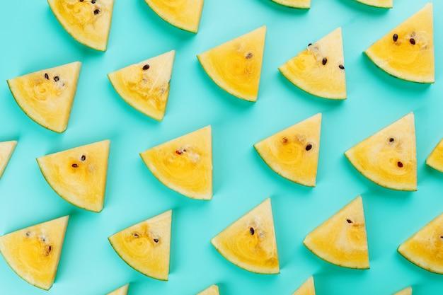 Muster von scheiben der frischen gelben wassermelone auf blau
