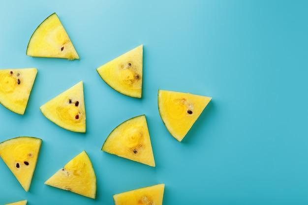 Muster von scheiben der frischen gelben wassermelone auf einem blau. von oben betrachten. freiraum