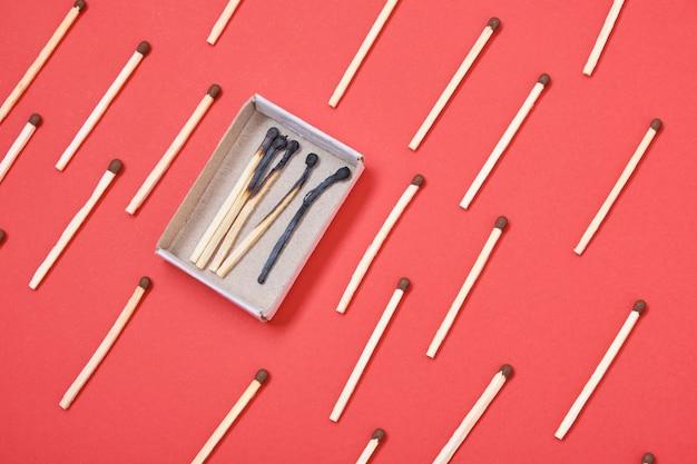 Muster von streichhölzern und eine schachtel mit verbrannten streichhölzern auf einem roten