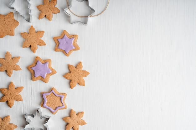 Muster von süßen sternförmigen lebkuchenplätzchen mit violettem zuckerguss, der auf weißem holztisch liegt