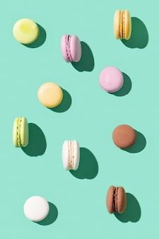 Muster von verschiedenen kuchenmakronen auf grünen mehrfarbigen französischen keksmakronen