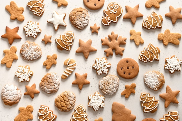Muster von verschiedenen weihnachts hausgemachten lebkuchenplätzchen als schneeflocken, sterne, weihnachtsbaum auf weißem hintergrund. abstrakter hintergrund des weihnachtsfestes.