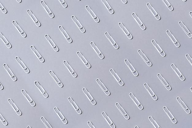 Muster von weißen büroklammern auf grauem hintergrund